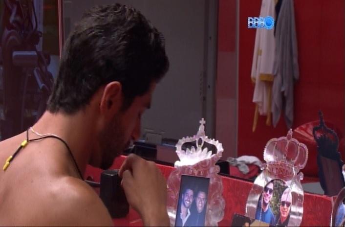 26.mar.2014 - Marcelo observa as fotos de seus familiares dispostas no quarto do líder e faz um sinal da cruz diante delas