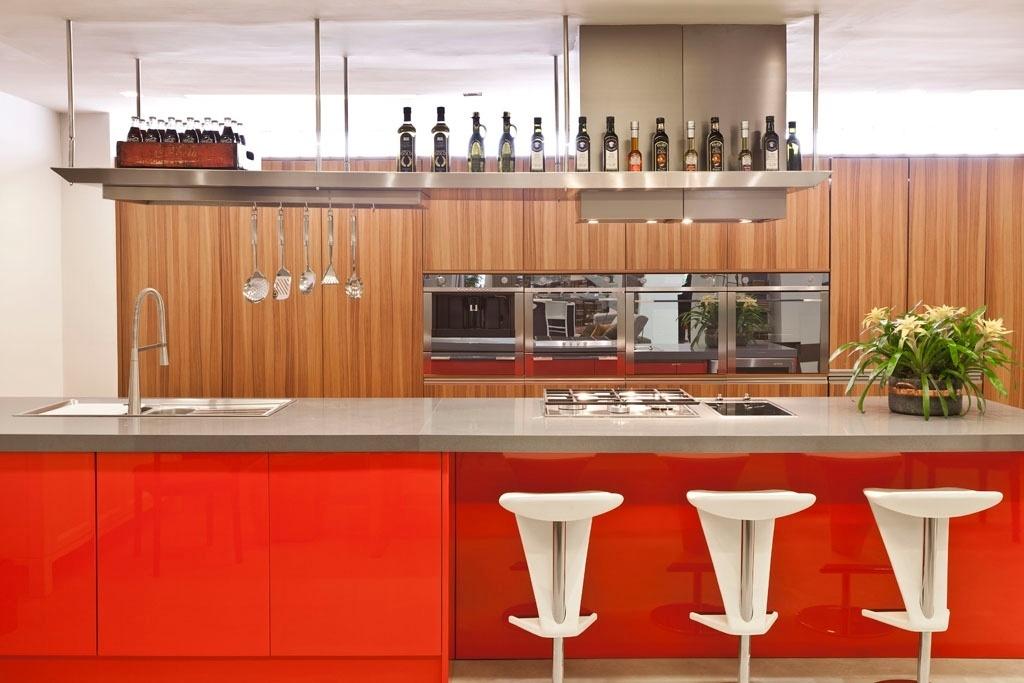 Para a cozinha americana desse apartamento em Belo Horizonte (MG), a arquiteta Simone Malacarne combinou materiais com diferentes texturas. Ao fundo, os armários Florense receberam acabamento laminado no padrão madeira. Já a bancada foi finalizada com pintura vermelha de alto brilho, que cria um contraste com as banquetas brancas