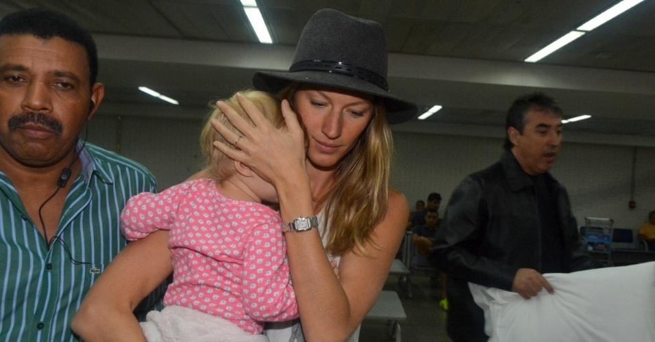 1.abr.2014 - Gisele Bündchen desembarca no aeroporto de Guarulhos, em São Paulo, com a filha Vivian Lake no colo e tenta tapar o rosto dela. A menina de um ano é fruto do casamento da top com o jogador de futebol americano Tom Brady. Gisele está na cidade para desfilar pela Colcci no SPFW