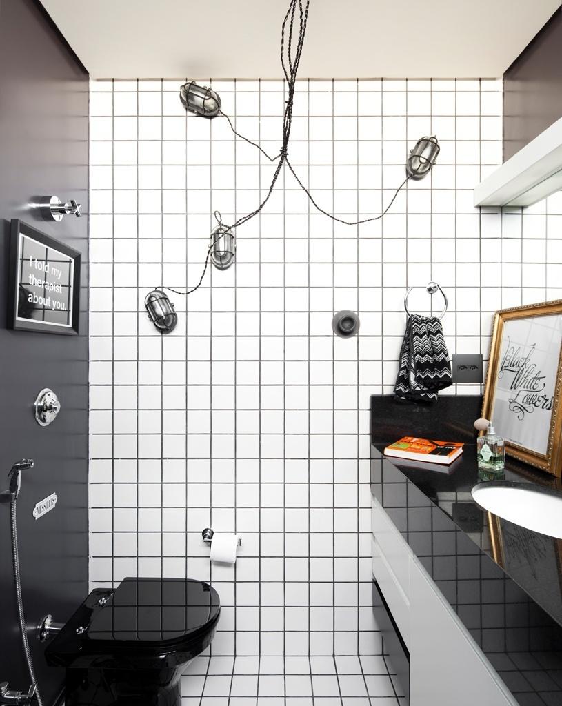 Em preto e branco, o banheiro do casal contrasta com os matizes vivos da maior parte dos ambientes ou a tenuidade dos espaços mais neutros, como um dos banheiros de hóspedes e a sala de jantar. Neste ponto do apartamento RO, uma parede poi pintada de preto e está associada a outra com azulejos brancos que seguem pelo piso. O destaque são as luminárias presas à parede como se
