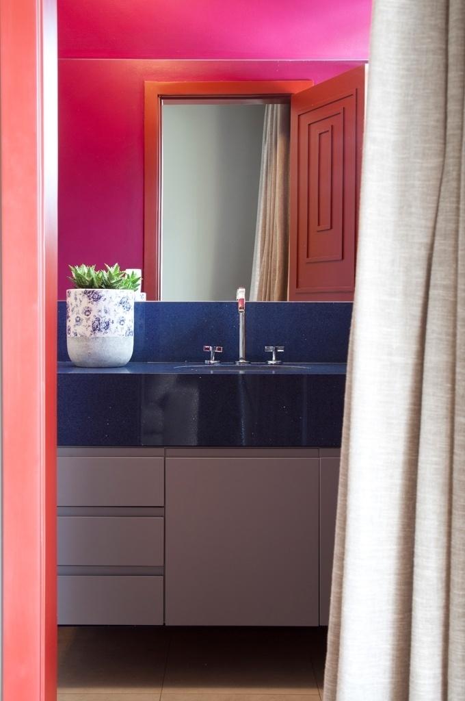 O banheiro dos hóspedes é composto por cores intensas, na quase totalidades das paredes e na porta. Para amenizar o impacto das cores quentes, a bancada recebeu dois matizes: azul marinho e cinza. O projeto para o apê RO, que venceu o prêmio