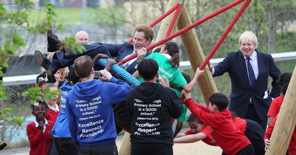 4.abr.2014 - Príncipe Harry brinca com crianças em balanço durante visita oficial ao Queen Elizabeth Olympic Park, em Londres