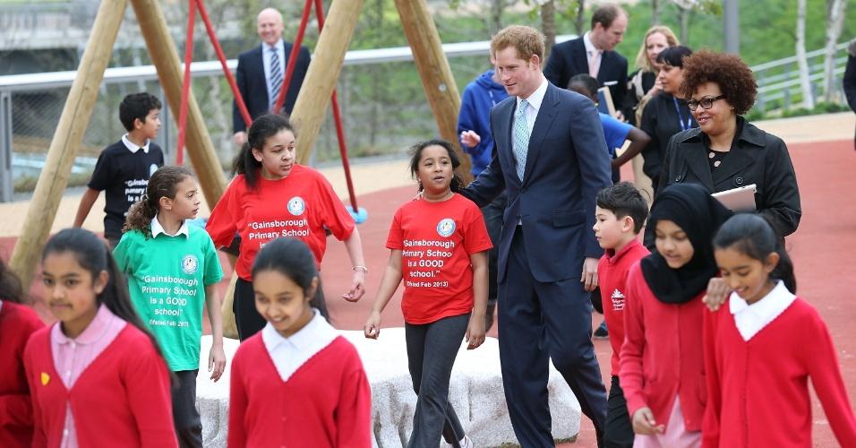 4.abr.2014 - Príncipe Harry se diverte com crianças durante visita oficial ao Queen Elizabeth Olympic Park, em Londres