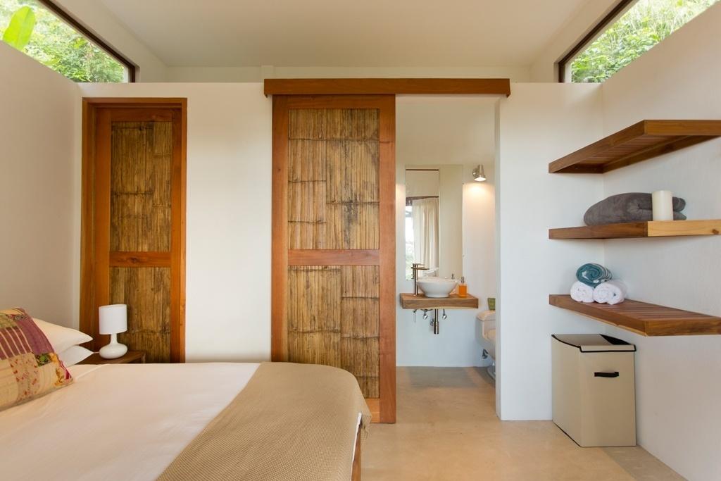 Na suíte menor, portas de bambu separam o banheiro do dormitório. A luz natural é intensificada por aberturas zenitais. De frente para o Pacífico da Costa Rica, a arquitetura da casa Flotanta é assinada por Benjamin Garcia Saxe