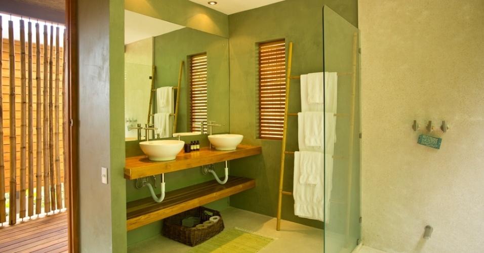 O banheiro é o cômodo mais privativo da casa Flotanta. Sua orientação é para a encosta verde, nos fundos da residência. Internamente, a cor da mata tropical é reproduzida nas paredes rústicas, em cimento. A madeira, matéria-prima protagonista no projeto de Benjamin Garcia Saxe, aparece na bancada e na veneziana, enquanto o porta-toalhas é confeccionado com bambus