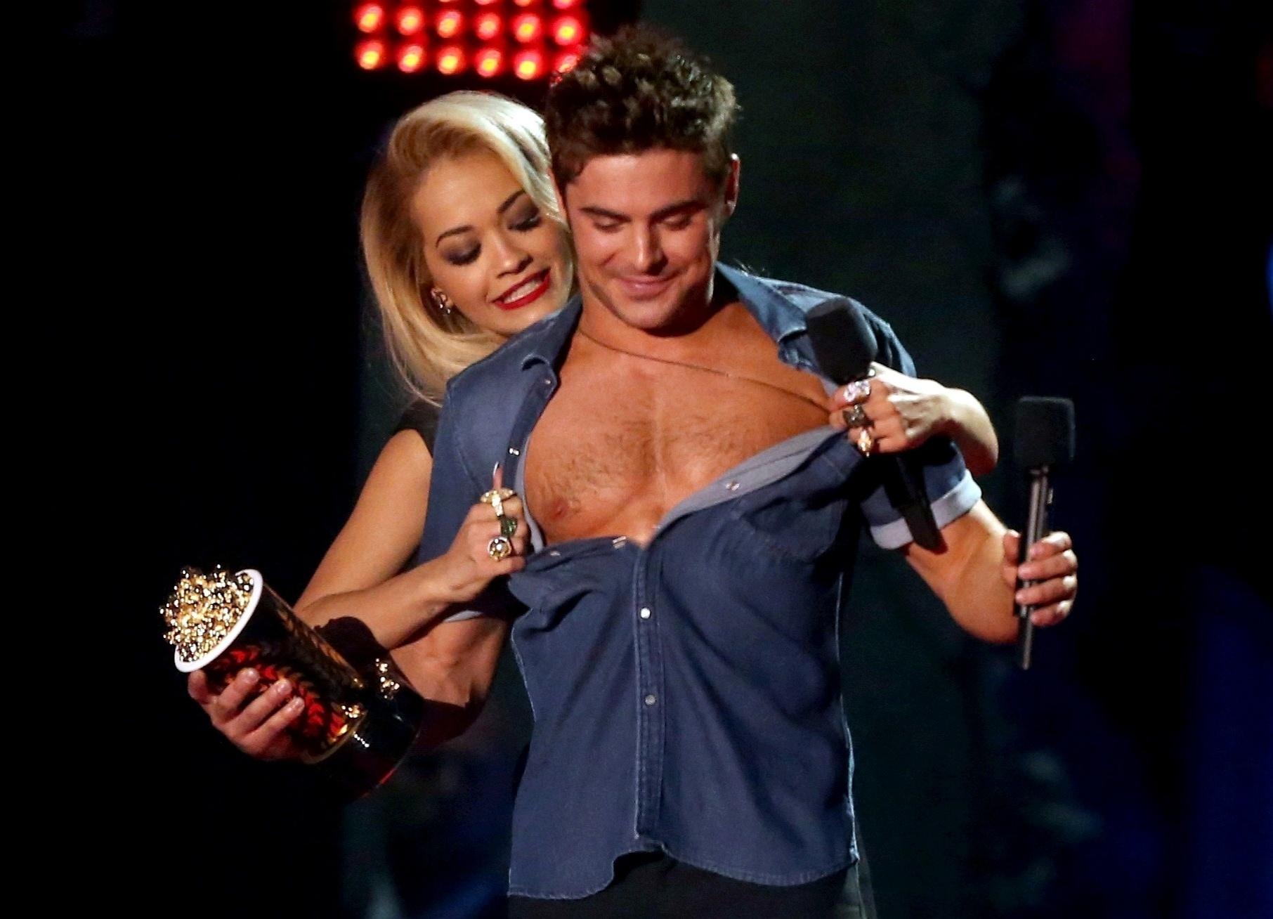 13.abril.2014 - Rita Ora tira a camisa de Zac Efron no MTV Movie Awards 2014, na noite deste domingo (13), no Nokia Theatre, em Los Angeles