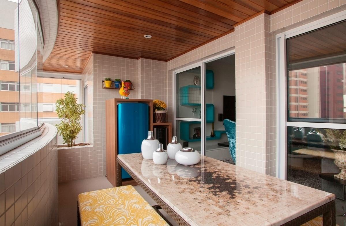 O espaço de 11m² transformou-se numa varanda gourmet com churrasqueira, bancos e uma grande mesa central, cujo tampo é feito com mosaico de pedras de mármore recortadas e resina