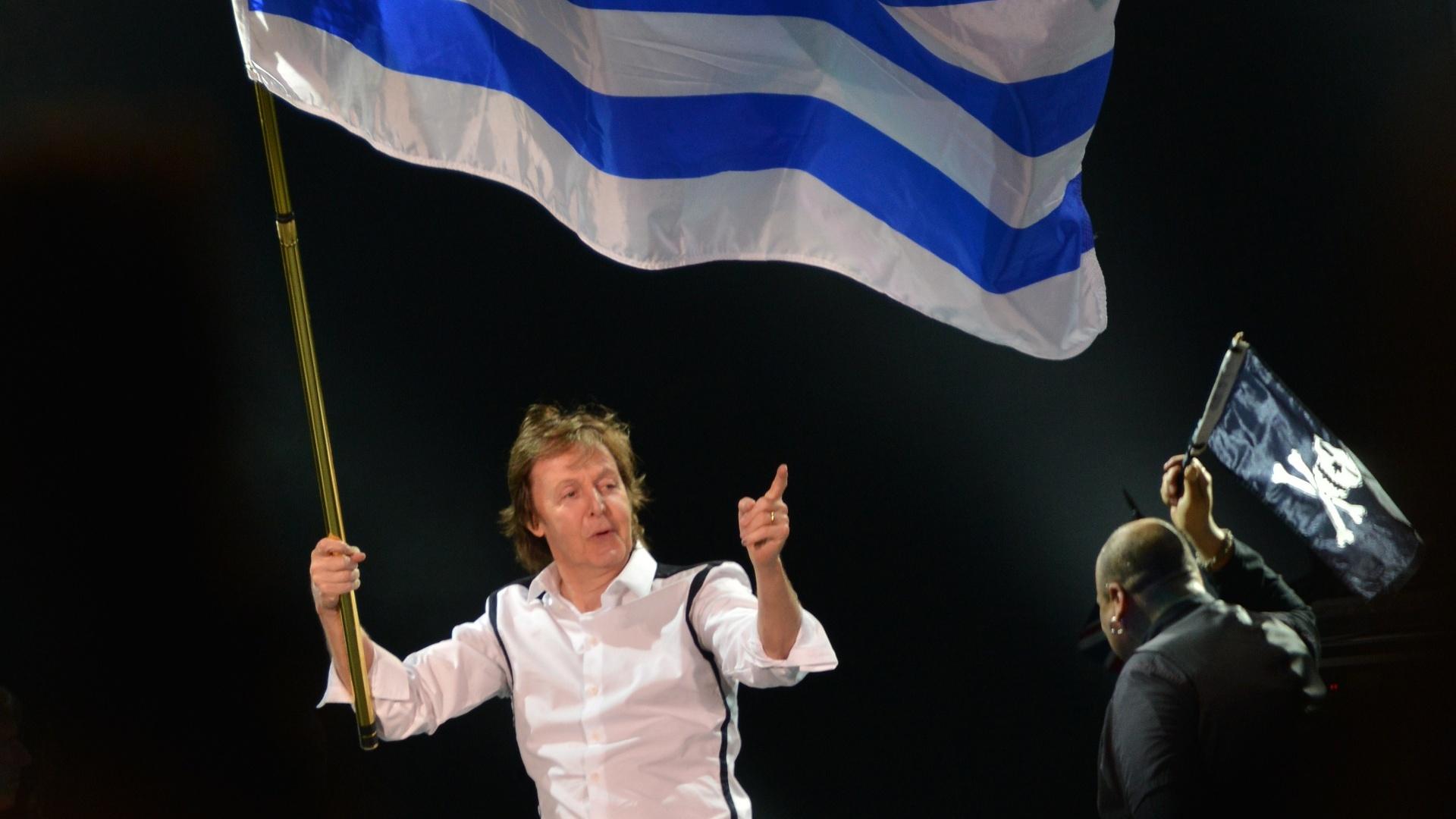 19.abr.2014 - Com a bandeira do Uruguai, Paul McCartney abre a etapa sul-americana de sua turnê
