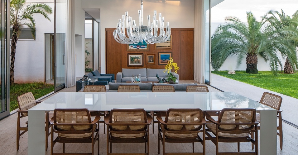 Aberto para o exterior nas duas laterais, o living recebe intensa luz natural e ventilação. Com ambientes integrados, jantar e estar, o espaço tem pé-direito duplo e móveis contemporâneos assinados, como as cadeiras do designer Sergio Rodrigues e a mesa da Dpot