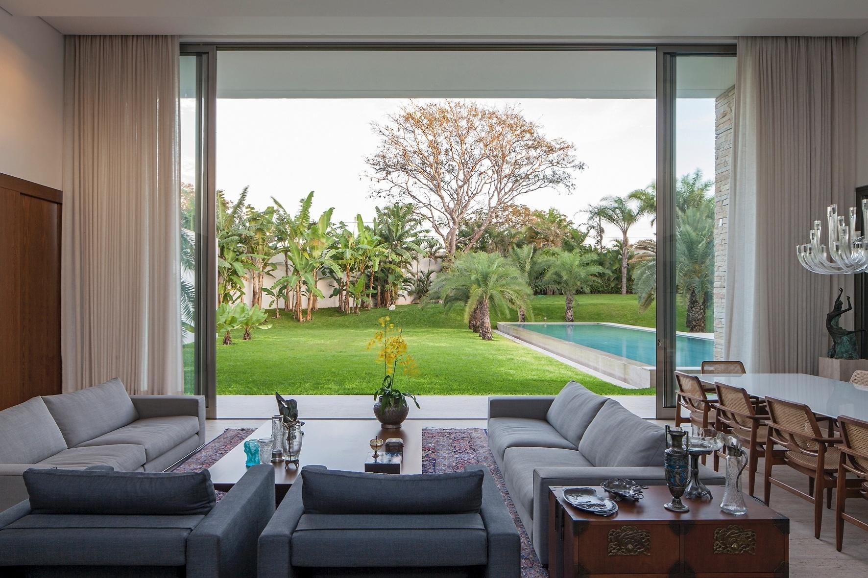 Com cores neutras e suaves, como o cinza, o estar possui atmosfera elegante e tranquila. Aberto para o exterior, o espaço tem vista para a piscina, o jardim com gramado e o pomar com árvores frutíferas