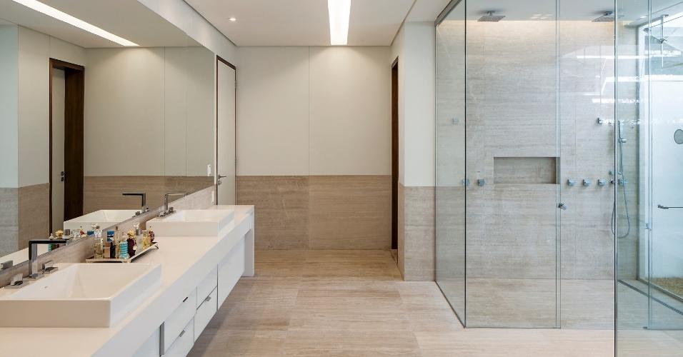 O banheiro da suíte do casal tem amplo espaço e conforto absoluto, com bancada extensa que embute duas cubas e generosa área para chuveiro. Destaque para as duas portas de acesso ao dormitório