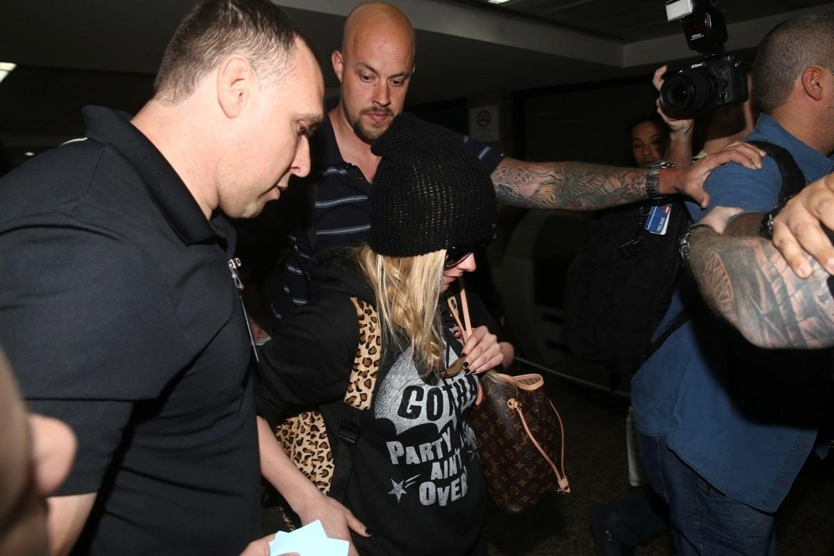 28.abr.2014- Avril Lavigne é cercada por seguranças ao chegar ao Brasil