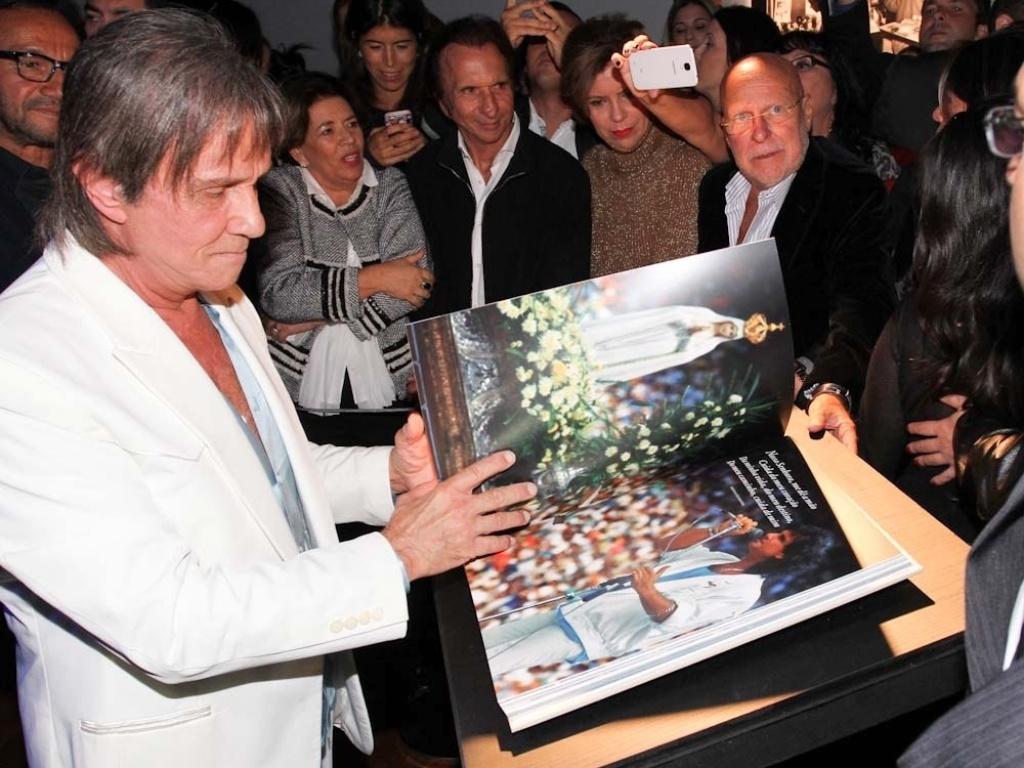 29.abr.2014 - Roberto Carlos recebe carinho de amigos ao abrir sua biografia fotográfica em lançamento, em São Paulo. A edição é limitada, com três mil exemplares, e tem o valor de R$ 4,5 mil cada. A obra chegará às livrarias de todo o país em lotes de 500 unidades por vez