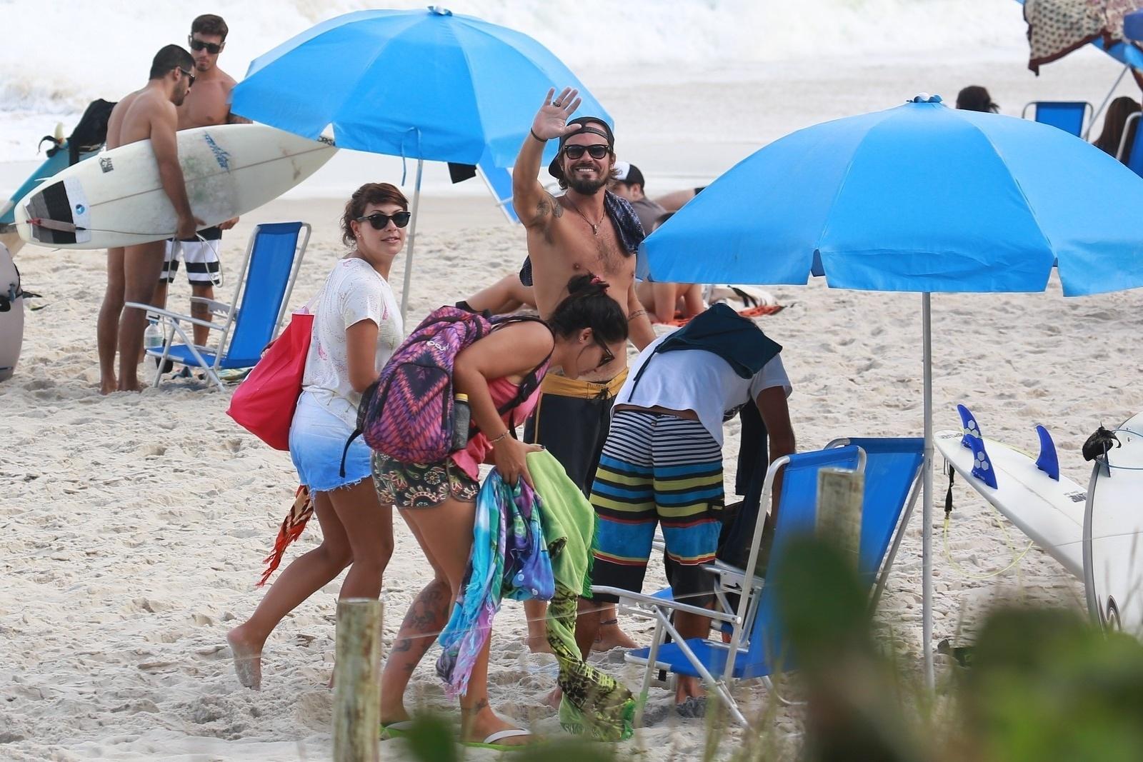 2.mai.2014 - Com turma de amigos, incluindo a atriz Fabíula Nascimento, o ator Paulinho Vilhena acena para fotógrafo na Prainha, no Rio de Janeiro