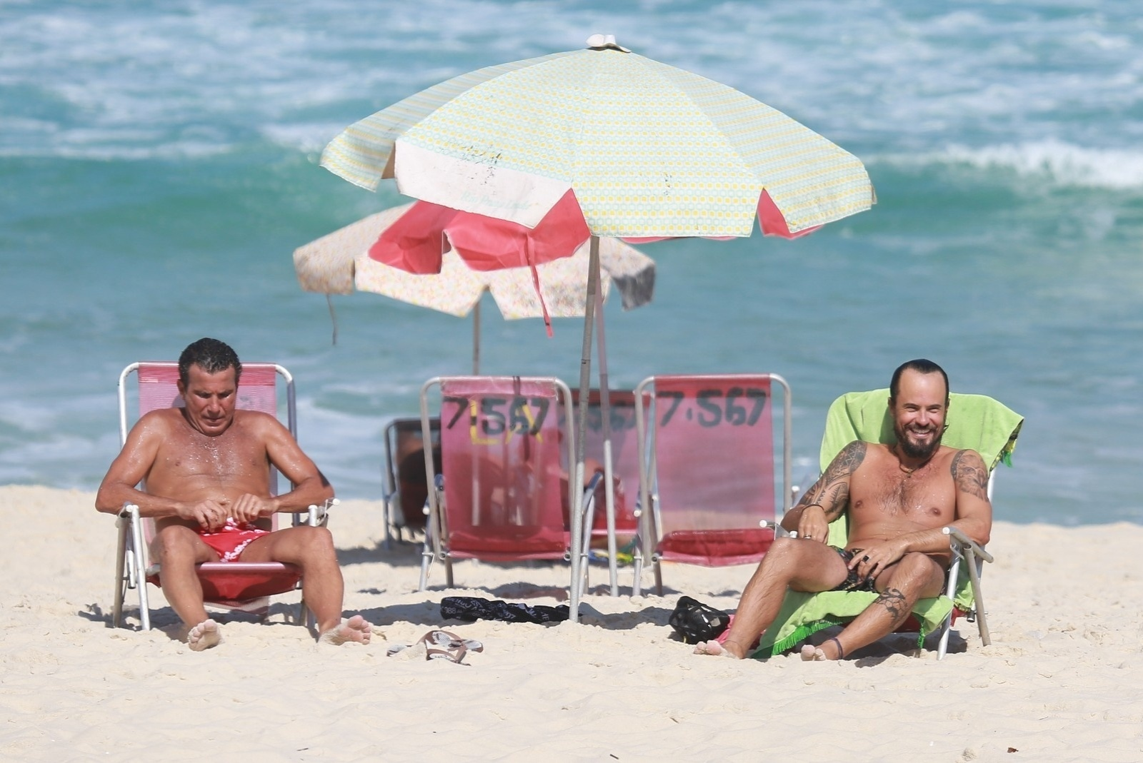 5.mai.2014 - Após mergulho, Paulinho Vilhena e Eri Johnson curtem bate-papo sob o guarda-sol na praia Recreio dos Bandeirantes, no Rio de Janeiro