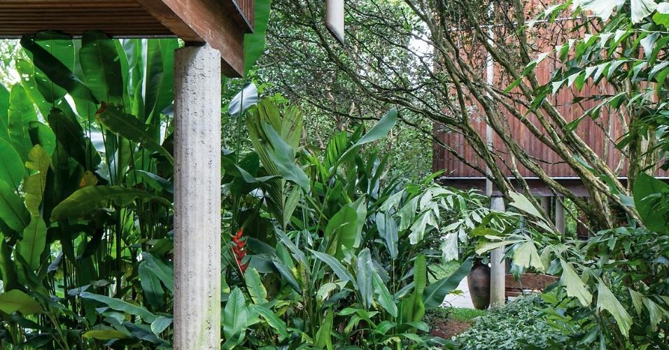 Jardins de uso comum com caminhos de pedras separam as casas da Vila Taguaí, todas projetadas dentro do mesmo conceito pela arquiteta Cristina Xavier e pelo engenheiro Hélio Olga. Do beiral da cobertura pende o tubo de captação da água pluvial, reutilizada na irrigação dos jardins