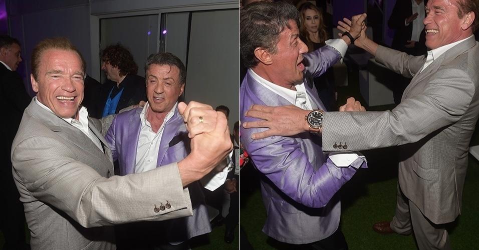18.mai.2014 - Descontraídos, Arnold Schwarzenegger e Sylvester Stallone dançam juntos durante um festa do filme