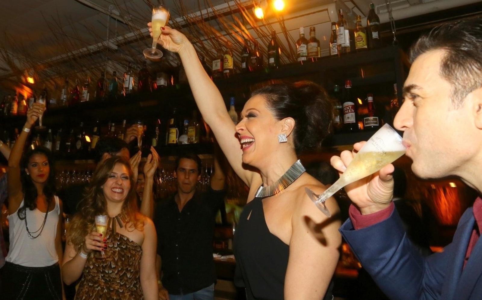 19.mai.2014 - Claudia Raia puxa um brinde para comemorar a estreia do musical