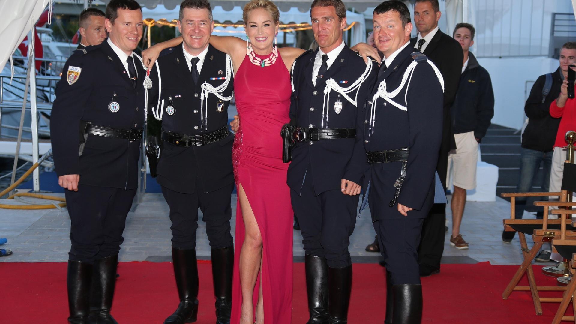 20.mai.2014 - Com vestido vermelho, Sharon Stone posa com policiais franceses antes de embarcar em iate onde prestigiaria uma festa