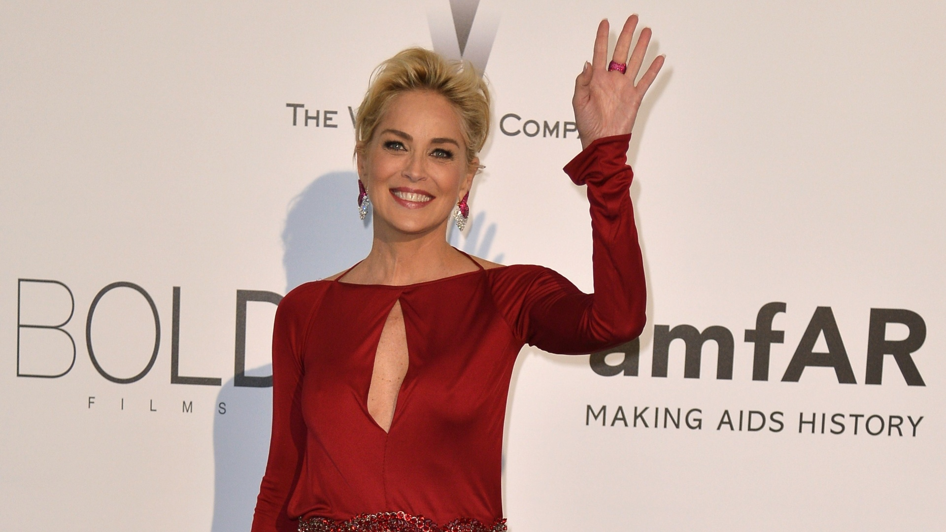 22.mai.2014 - Sharon Stone ousou no look ao usar um longo vermelho repleto de decotes durante o baile de gala da amfAR em Cannes, na França. Em boa forma, a atriz optou por usar o modelito sem sutiã. Sorridente, Sharon mostrou simpatia ao acenar para as fotos