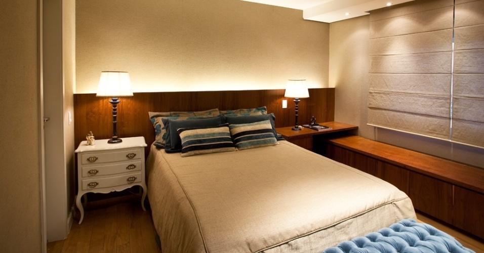 Baseado em tons claros de bege, este dormitório ganhou vida com as pinceladas de azul (em variações que vão do pastel, no banco  junto ao pé da cama, ao escuro, nas almofadas) e calor com o mobiliário amadeirado planejado pelo arquiteto Maurício Karam. A sinuosidade dos móveis