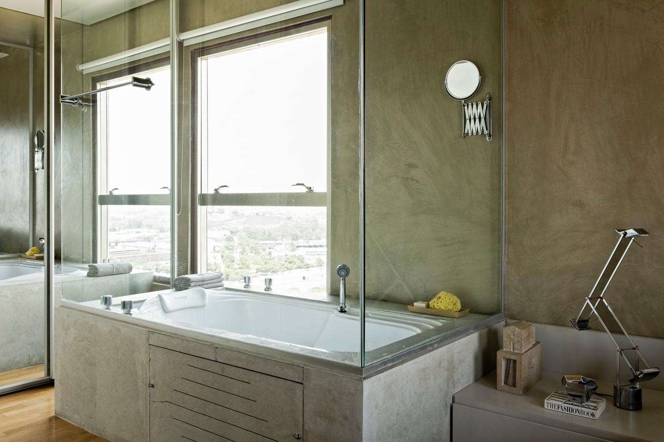 banheira revestida em limestone recebeu fechamento em vidro na parte  #886E43 1344 896