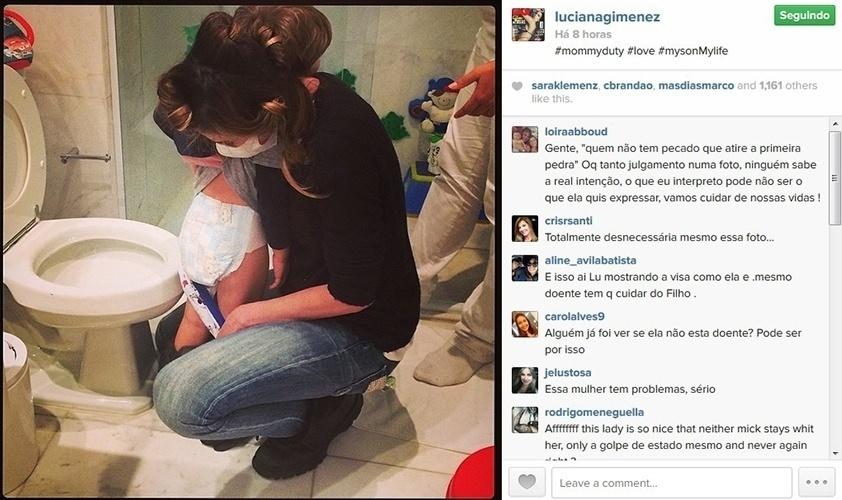 28.mai.2014 - De máscara, Luciana Gimenez leva o filho mais novo, Lorenzo, ao banheiro e troca a fralda dele