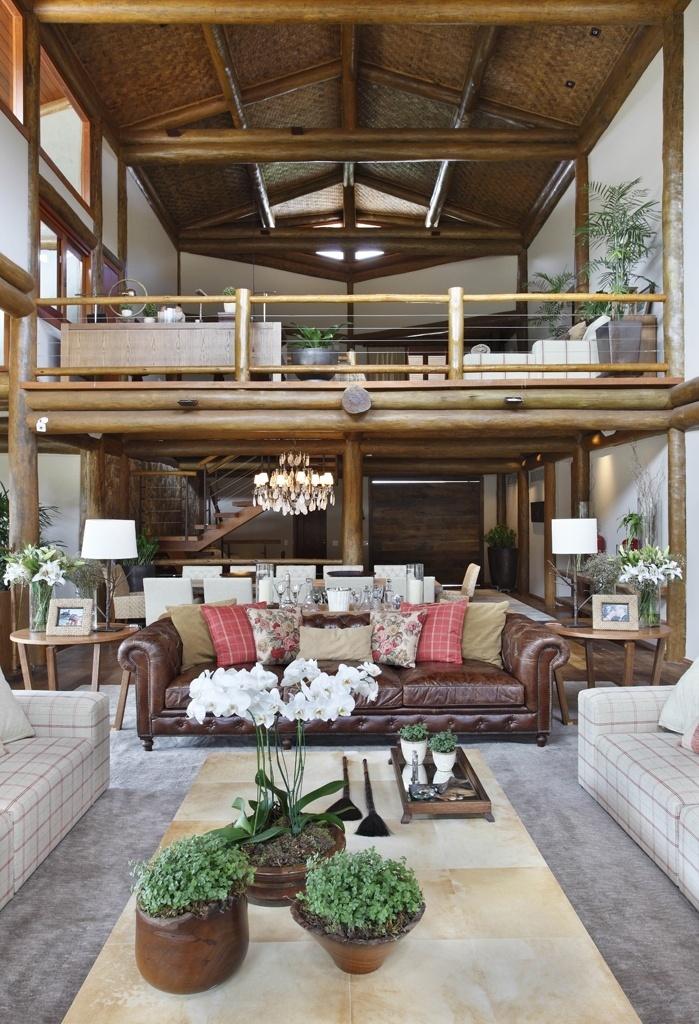 Projetado pela arquiteta Debora Aguiar, o living tem pé-direito duplo e parte da estrutura composta por toras de madeira. No centro do estar, a mesa revestida por pergaminho alia-se ao sofá de couro, completando o clima rústico
