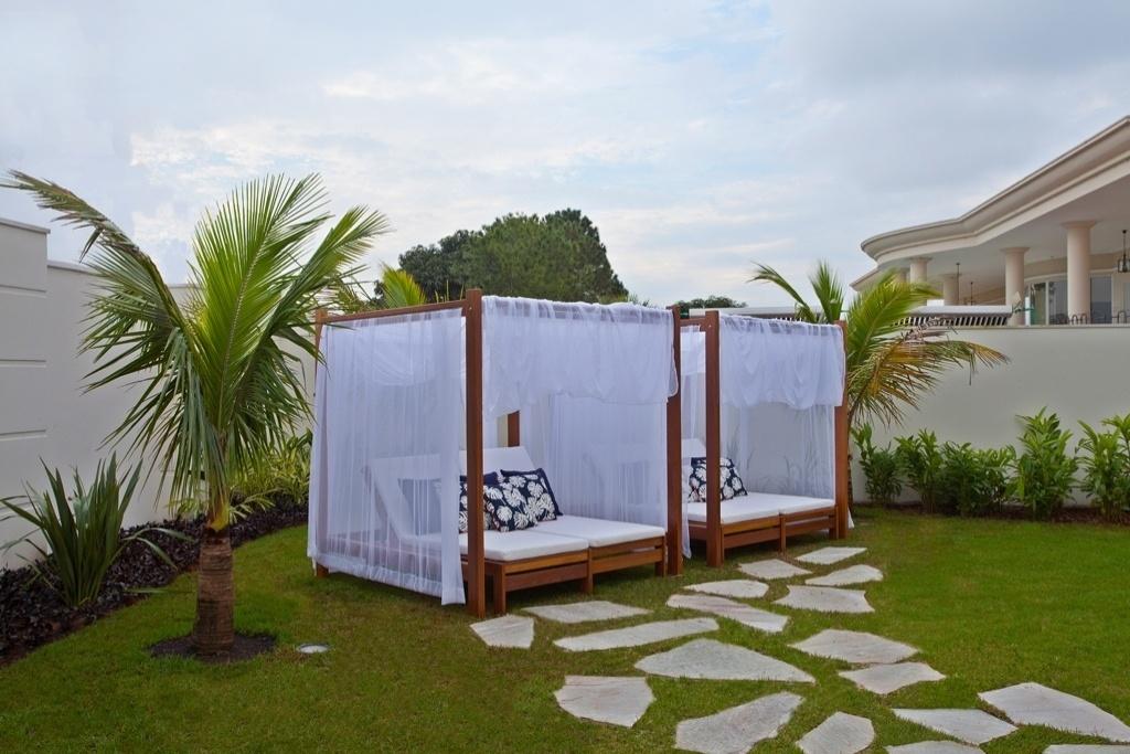 Dois gazebos instalados no jardim proporcionam um espaço dedicado ao relaxamento e à contemplação em meio às palmeiras. O projeto de arquitetura da casa de veraneio do jogador Oscar, em Americana (SP), é de Aquiles Kílaris. Já o design de interiores e o paisagismo têm a assinatura de Iara Kílaris