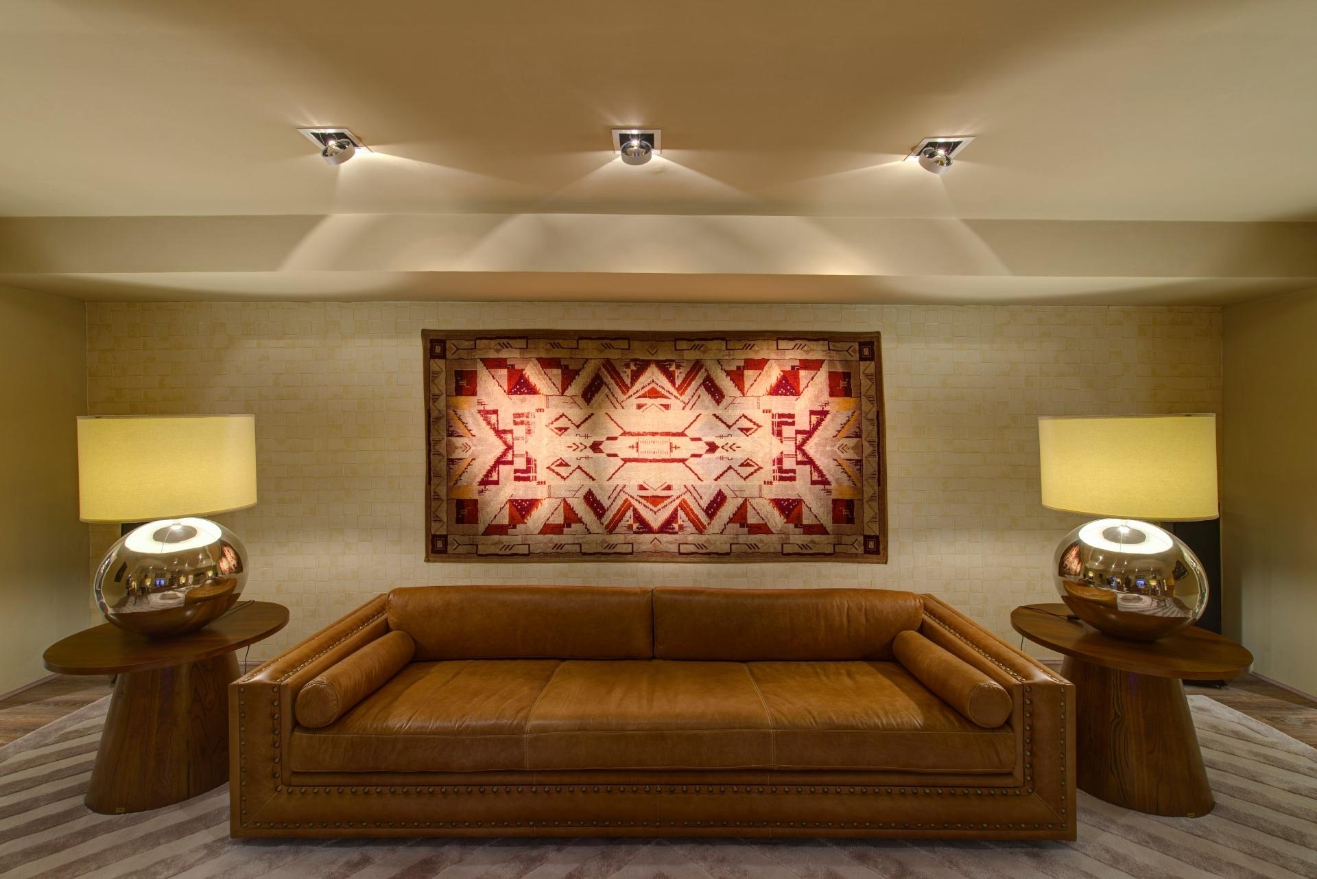 Dar novos usos a objetos - No Living, o arquiteto João Mansur decorou uma das paredes com um tapete. O ambiente tem uma proposta limpa e atemporal, composta por cores sóbrias e disposição simétrica dos elementos