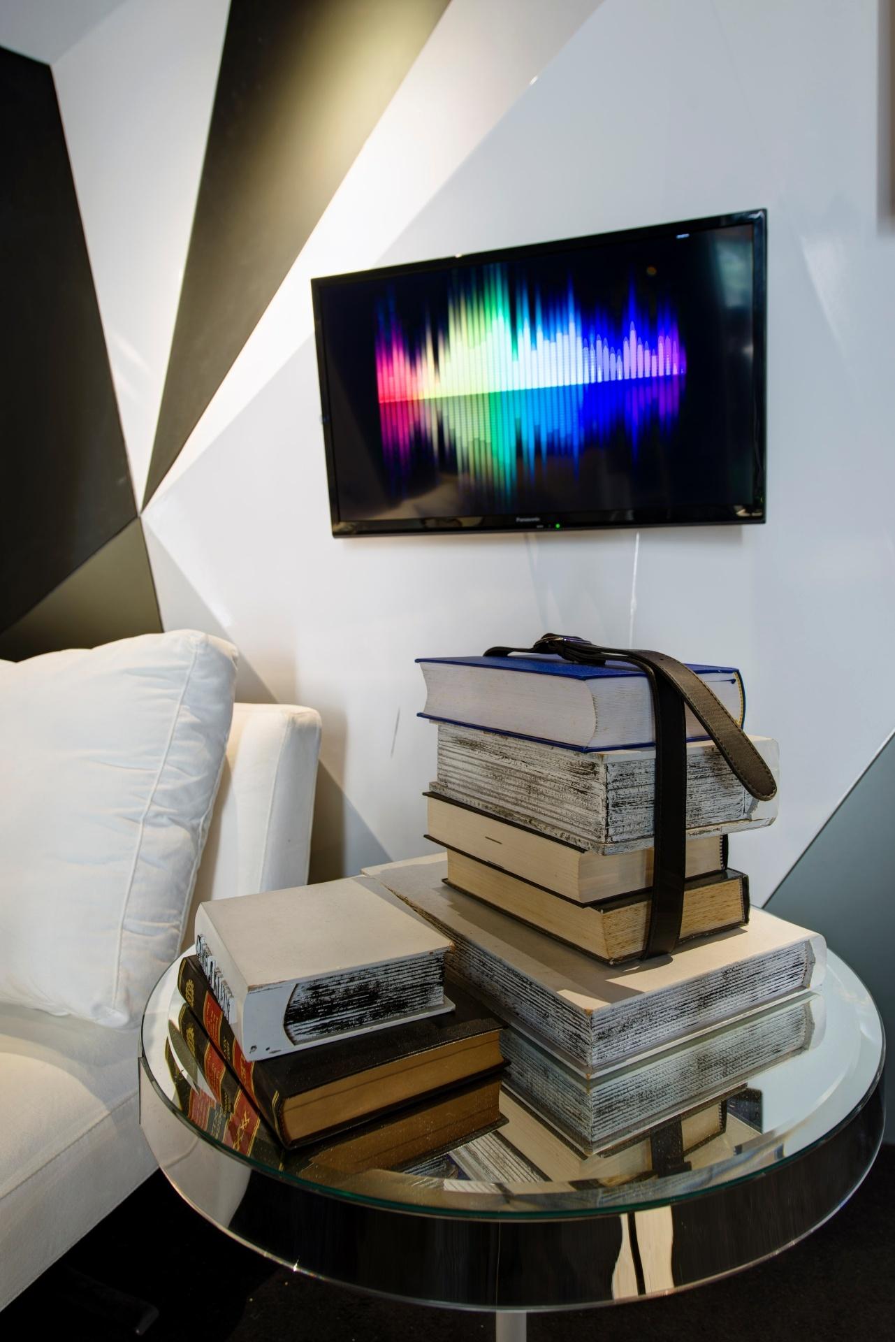 Livros como elemento decorativo - No Lounge Cosmopolita, Camila Klein dispôs livros sobre a mesa lateral. Para dar um toque despojado, um cinto contorna e prende uma das pilhas