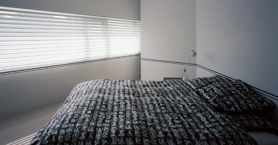 No quarto do casal, as persianas são da linha Silhouete (Hunter Douglas), com tecido que permite a entrada de luz filtrada e suave, de forma que a cama pudesse ser posicionada de frente para o vão de abertura (janelas em caixilhos de alumínio). As paredes em painéis de gesso acartonado estão isoladas térmica e acusticamente por uma camada interna de espuma de poliuretano, o que aumenta a privacidade do ambiente. Seu piso em carpete aquece o espaço íntimo
