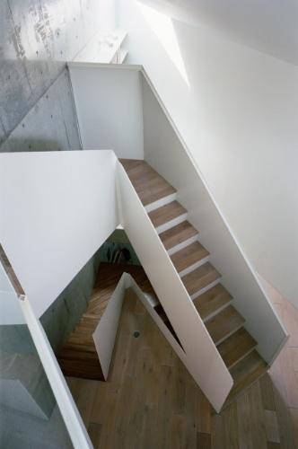 O hall de circulação vertical tem pé direito duplo, a partir do primeiro andar. No terceiro pavimento, o lance de escadas leva ao dormitório do casal. O guarda-corpo desenhado pelo arquiteto Tsuyoshi Ando é executado em chapas de aço que levam pintura esmaltada. Sua geometria é reta e sóbria, resumindo o próprio conceito arquitetônico para a CasaTN, que fica em Tóquio, no Japão