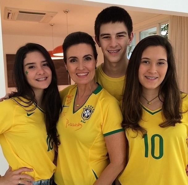 12.jun.2014 - Vestida com a camisa do Brasil, Fátima Bernardes curte a Copa com os filhos trigêmeos também devidamente uniformizados.