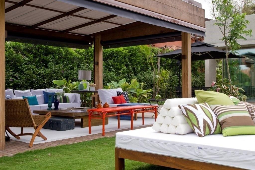 Assim como no living, a decoradora Marília Veiga escolheu o branco como base para o mobiliário do terraço. A madeira está presente na poltrona e na mesa de centro, enquanto as cores vivas prevalecem nas almofadas e no banco alaranjado vibrante. A casa de praia fica próxima à cidade de Paraty (RJ)