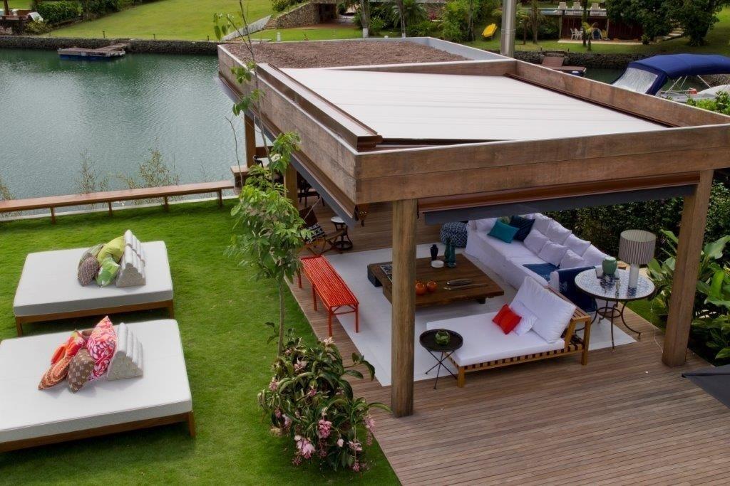 Bem próximo ao lago do condomínio fechado, o terraço tem móveis confortáveis e uma decoração baseada no branco e em cores fortes pinceladas nos objetos. A decoradora Marília Veiga assina o projeto de interiores da casa de praia