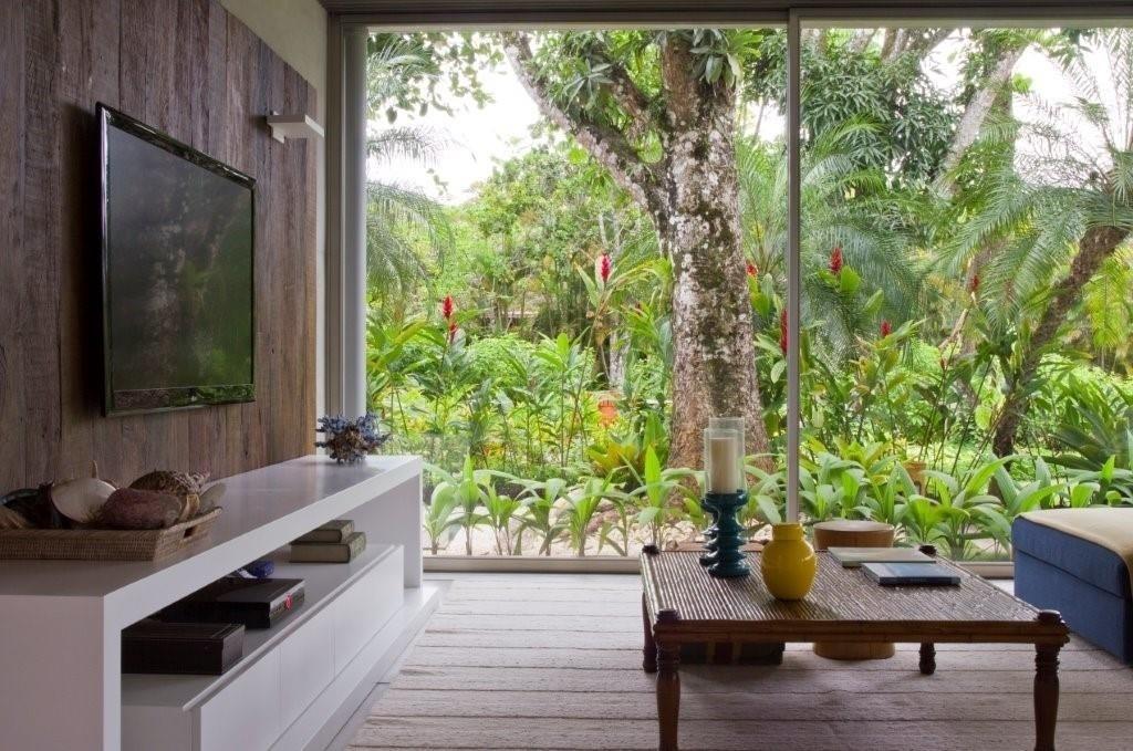 Com fechamento em vidro, o home theater se integra à vegetação que cerca a casa de praia. No ambiente, o painel da TV em madeira de demolição é o destaque da decoração criada por Marília Veiga
