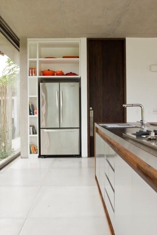 Com pia e cooktop, a bancada da área gourmet combina aço inox e madeira de demolição. O ambiente tem ainda geladeira embutida e espaços para acomodar os utensílios da cozinha. Quem assina o projeto de interiores da casa de praia é a decoradora Marília Veiga