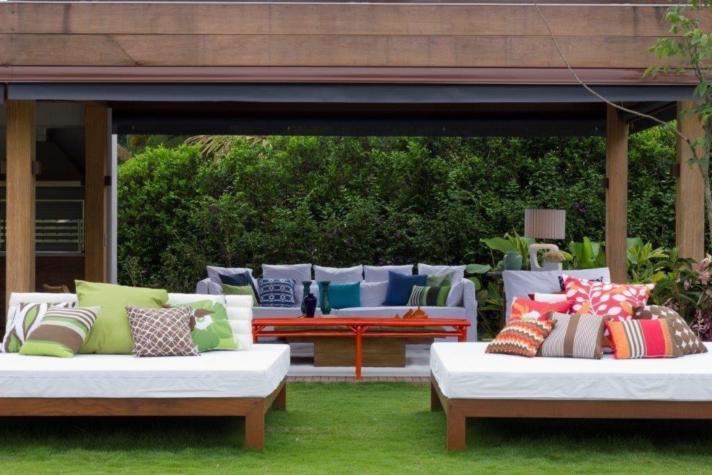 Dispostas em frente ao terraço, as grandes chaises são revestidas por tecido impermeável e decoradas com almofadas estampadas e coloridas. Para o projeto de interiores da casa de praia, a decoradora Marília Veiga usou as cores de forma pontual nos objetos, em harmonia com o verde da paisagem