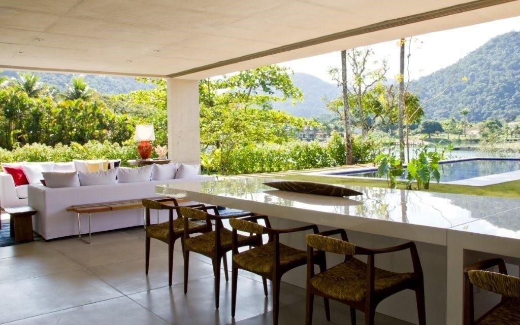 Integrado à sala de estar e à área da piscina, o espaço gourmet possui uma extensa mesa de jantar (Clami), em laca branca, com cadeiras em madeira e fibra (Clami). A decoração da casa de praia, situada próxima à cidade de Paraty (RJ), é uma criação de Marília Veiga
