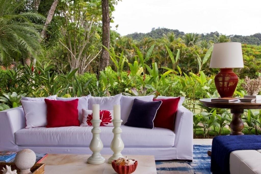 No ambiente de estar, Marília Veiga partiu das tonalidades azuis do tapete (By Kamy) para definir a paleta de cores. Sobre o sofá branco, a decoradora usou almofadas marinho e vermelhas. Esse último tom também marca a base da luminária sobre a mesa lateral. Destaque ainda para a integração do espaço com o verde da paisagem