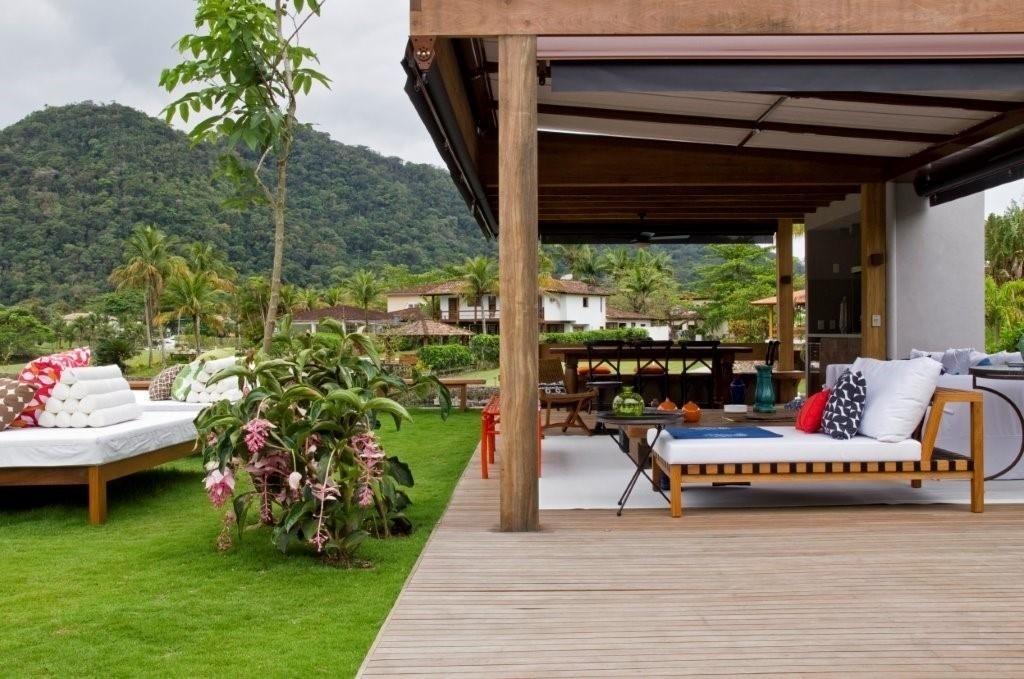 No projeto de interiores da casa de praia, a decoradora Marília Veiga compôs um terraço confortável, equipado com espreguiçadeiras. Sob a mesma estrutura de madeira, estão o espaço de estar e a área da churrasqueira (ao fundo)