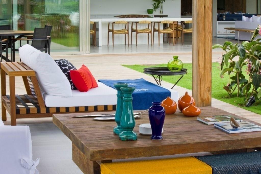 No terraço da casa de praia, a decoradora Marília Veiga pontua com cores vibrantes os detalhes, como os objetos sobre a mesa de centro em madeira rústica