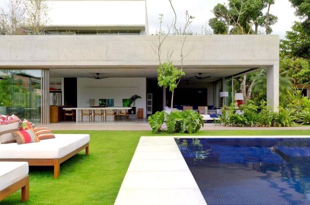 Por conta dos panos de vidro móveis, o living se abre à área da piscina e ao verde que circunda a casa de praia na região de Paraty (RJ). O projeto de interiores é assinado por Marília Veiga