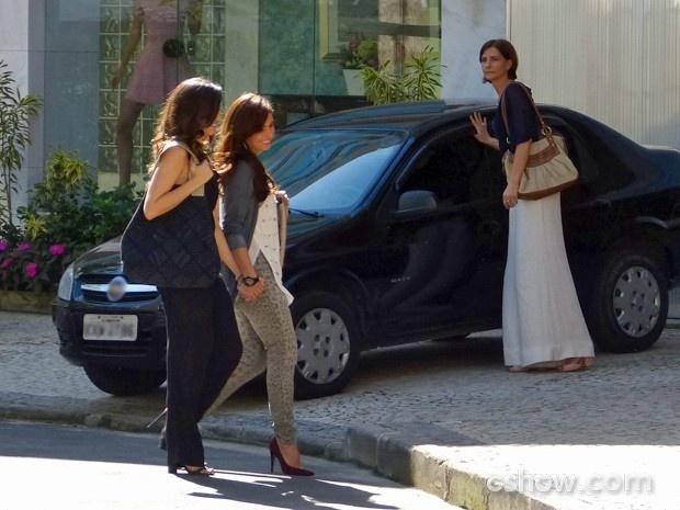 Clara caminha sorridente de mãos dadas com Marina e, ao avistar uma conhecida, solta a mão da fotógrafa