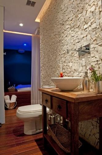 O piso do lavabo foi executado com um deck de madeira pau d'arco e o aparador de madeira, para apoio da cuba, foi garimpado em Embu das Artes (SP). O lavabo está ligado ao spa, com hidromassagem, no Apartamento Alto de Pinheiros, reformado pelos arquitetos Gabriel Magalhães e Luiz Cláudio Souza