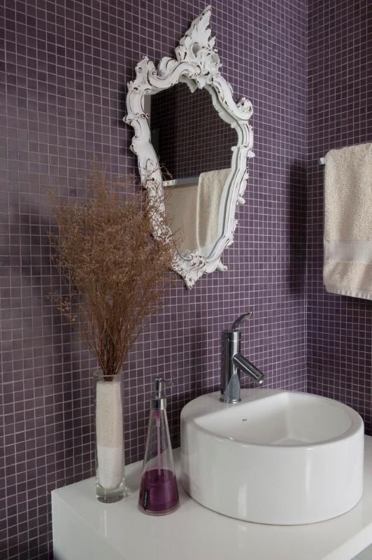 O banheiro de hóspedes do apartamento Alto de Pinheiros teve o piso revestido por pastilhas de vidro roxas da Colormix e paredes e nichos recobertos por unidades da mesma marca (2 cm x 2 cm) na cor lilás. A bancada é de estrutura cristalizada a base de vidro e pó de mármore e o espelho foi garimpado em Embu das Artes (SP). A reforma da residência é assinada pelos arquitetos Gabriel Magalhães e Luiz Cláudio Souza