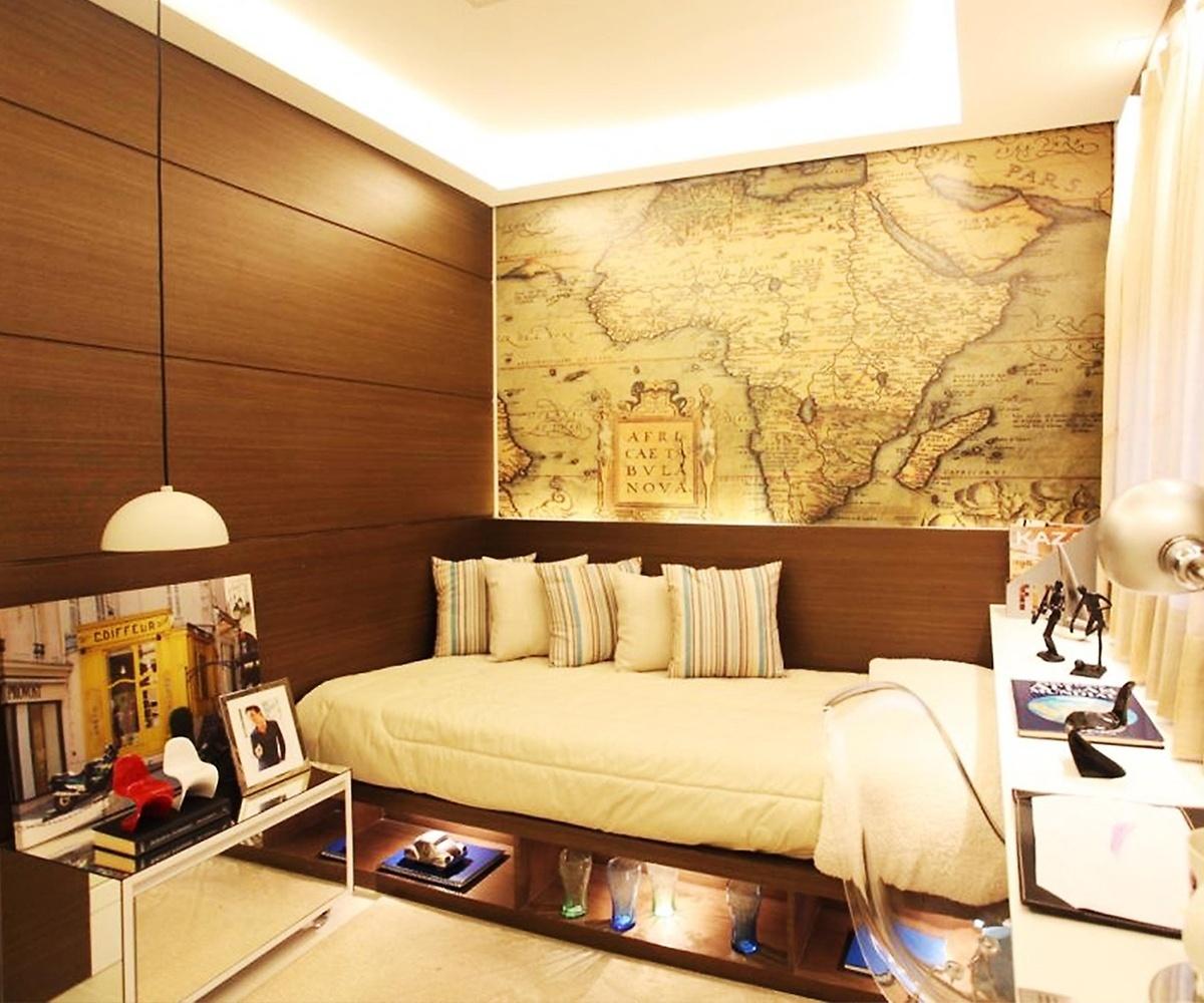 No quarto de um rapaz de 17 anos que gosta de viajar e de estudar a história do mundo, o papel de parede estampado com a ilustração de um mapa antigo foi usado para compor um painel, sobre a cama. Para valorizar a imagem, a arquiteta Camila Klein planejou a iluminação focada e embutida na marcenaria