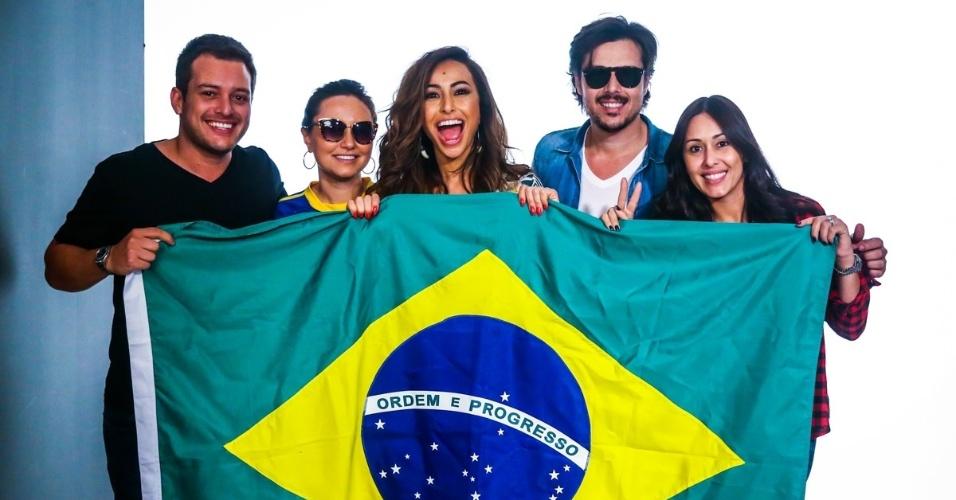 24.jun.2014 - A apresentadora Sabrina Sato posa segurando a bandeira do Brasil com a equipe de produção de uma campanha publicitária para a uma marca de roupas feminina, em São Paulo