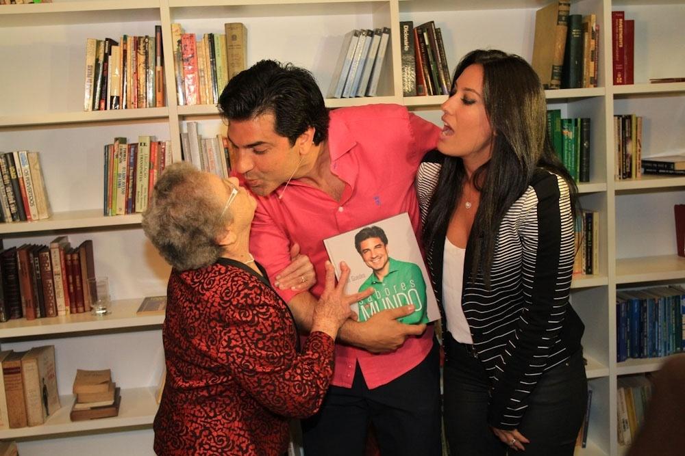 24.jun.2014 - Palmirinha dá selinho em Edu Guedes durante lançamento do livro